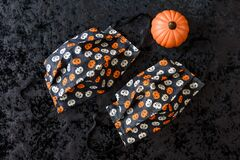 Free Two Orange And Cream Colored Pumpkin Patterned Fabric Face Masks, With A Ceramic Pumpkin, On A Black Background Royalty Free Stock Photography - 196731987