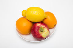 Two orange and apple fruits with one lemon. On white plate Stock Photography