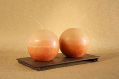 Two orange balls candle. Candles balls on golden textured paper at still life stock photography