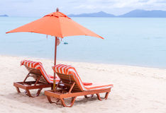 Two orange bed and umbrella on the beach. Royalty Free Stock Image