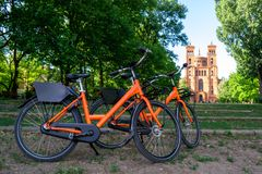 Two orange bicycles parked towards St. Thomas protestant church Thomaskirche in Berlin, Germany. Urban bike share concept. For weekend gateaways and sightseeing stock images