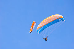 Two Orange blue bright Paragliders in blue sky. Paraglider in blue sky. Sport and hobby Royalty Free Stock Photo