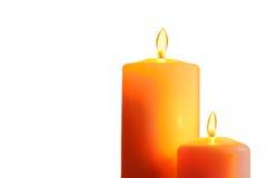 Two orange burning candles on white background Royalty Free Stock Image