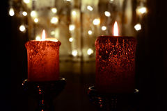 Two orange candles over christmas lights Stock Images