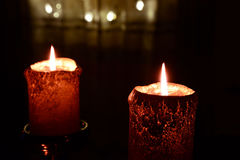 Two orange candles over christmas lights Royalty Free Stock Images