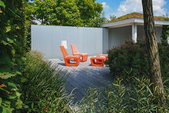 Two orange chair with floor lamp in a recreation area in the gar Stock Photo