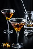 Two Orange Citrus Martinis stirred. Two orange citrus martini beverages with beaker, swizzle spoon, and jigger Royalty Free Stock Images