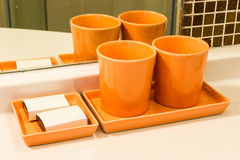 Two orange cup and Toothbrush on a Basin Stock Images