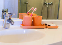 Two orange cup and Toothbrush on a Basin Stock Photography