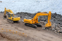 Two orange excavators Royalty Free Stock Photo