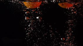 Two orange falls into water super slow motion video, orange backlight. Clip stock footage