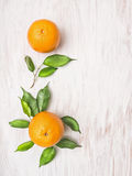 Two orange fruits with green leaves on withe wooden background. Top view Royalty Free Stock Photo