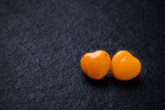 Two orange heart shaped pills or candy on grunge Royalty Free Stock Photo