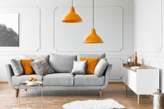 Two orange lamps above grey scandinavian couch with pillows. Real photo royalty free stock image