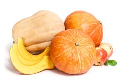 Two orange and one yellow pumpkins with three slices , two apples. With leaves isolated on white royalty free stock photos