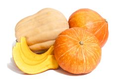 Two orange and one yellow pumpkins with three slices. On white royalty free stock image