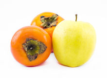 Two orange persimmons and an yellow apple on a white background Stock Photos