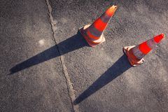 Two orange road cones on the gray asphalt Royalty Free Stock Images