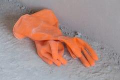 Two orange rubber gloves on concrete flloor Stock Image