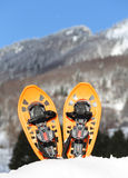 Two orange snowshoes in mountains in winter Stock Photos