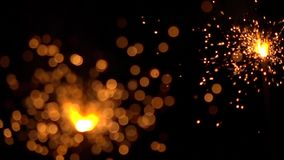 Two orange sparklers against dark background. Super slow motion shallow focus video, 500 fps stock footage