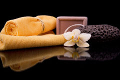 Two orange terry towels and soap handmade orchid flower Royalty Free Stock Photos