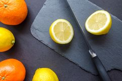Two Orange and Three Lemons on Gray Surface Royalty Free Stock Photography