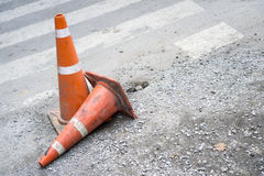 Two orange traffic cones on damage concrete road. One standing and the other one falling by crosswalk Royalty Free Stock Photo