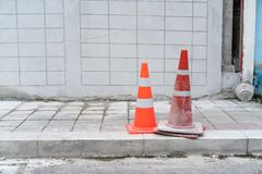 Two orange traffic cones on footpath concrete road. Two orange traffic cones on footpath concrete and road Stock Photography