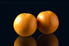 Two oranges on black background. With mirror image appearing below Stock Images