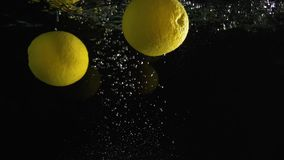 Oranges falling into water shot against black background. Two oranges falling into water super slow motion shot against black background stock footage