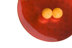 Two oranges in lacquered plate. Two oranges in a huge red lacquered plate separated on white background Stock Photos