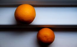 Two oranges one orange is slightly higher than the other on a wh Stock Images