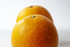 Two oranges placed behind each other isolated on white backgroun royalty free stock photo