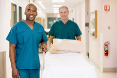 Two Orderlies Pushing Bed Down A Hospital Corridor Stock Photo