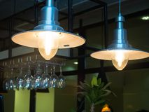 Two ordinary bar chandeliers with vine glasses royalty free stock photo