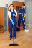 Two ordinary cleaners cleaning floor. In room Stock Photography