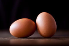 Two organic eggs on rural tabletop. Closeup of two organic eggs on a brown rural table top Stock Photos