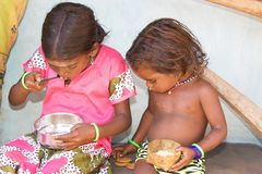 Two Orissa tribal children are eating Royalty Free Stock Photos