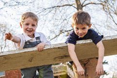 Two ornery  boys on swing. One boy throwing dirt while boys swinging  on white weathered board Stock Photography