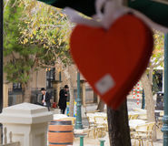 Two Orthodox Jews, dressed in a black coat and hat, looking at the street to offer pray before Shabbat and big red heart is betwee stock photography