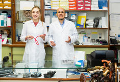Two orthopedists working in special store with orthopaedic goods. Two positive spanish orthopedists working in special store with orthopaedic goods royalty free stock image