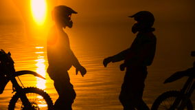 Two other motorcyclists met at beoregu river at sunset. They are happy to see each other and greet. Silhouette against stock video