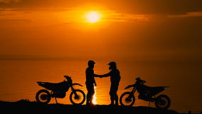 Two other motorcyclists met at beoregu river at sunset. They are happy to see each other and greet. Silhouette against. The background of water and sky stock video