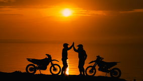 Two other motorcyclists met at beoregu river at sunset. They are happy to see each other and greet. Silhouette against stock footage