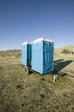 Two out houses, mobile blue bathrooms, sit on trailer in the middle of a field in Ventura County, California off of highway 33 nea Stock Image