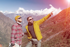 Two outdoor Men staying on Mountain Trail pointing old style. Two smiling Men in sporty clothing staying on Mountain Trail and pointing with Hand on Summit or Stock Images