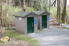 Two outdoor washrooms one for males and one for females. Each having the appropriate signage and green doors Stock Photos