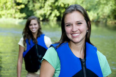 Two outdoorsy females with life jackets. Two outdoorsy active young adult women with life jackets in the river Stock Image