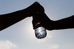 Two outstretched hands closeup holding water bottle. On blue sky background Stock Image